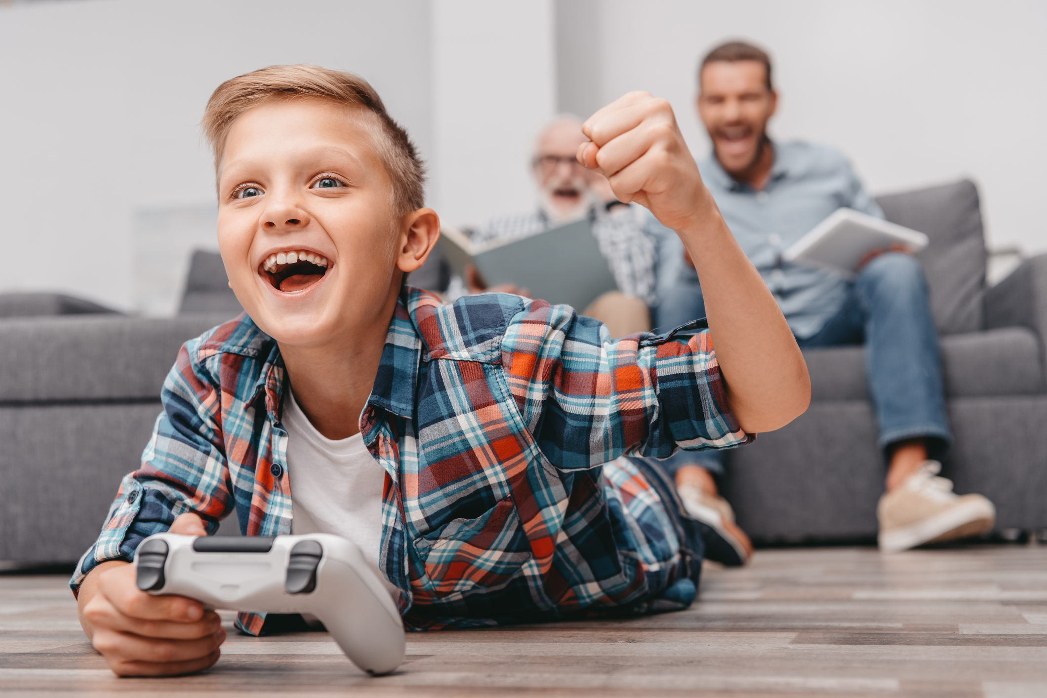 Little boy lying with gamepad on floor cheering, while his father and grandfather are watching him